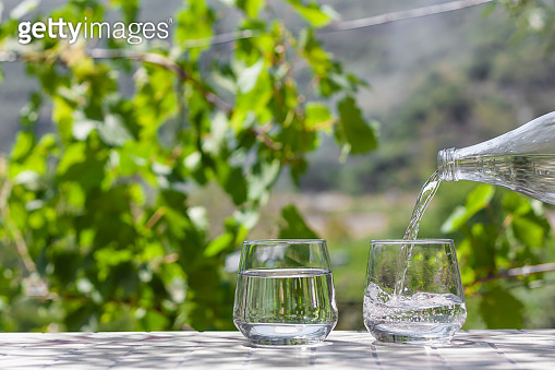 Fersh, clean, drink water pouring in to glass from a glass bottle. Select focus blurred nature background. Healthy lifestyle, water balance control, skin care concept.