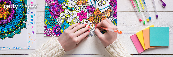 Adult coloring book, stress relieving trend. Art therapy, mental health, creativity and mindfulness concept. Flat lay close up on woman hands coloring an adult coloring book web banner.