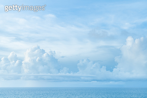 Bali beach scene - turquoise Indian ocean and cloudy sky.
