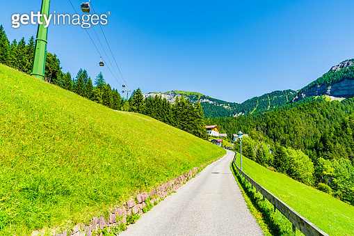 Road, leading to mountains. Italy - Dolomites mountains in a sunny cloudless day.