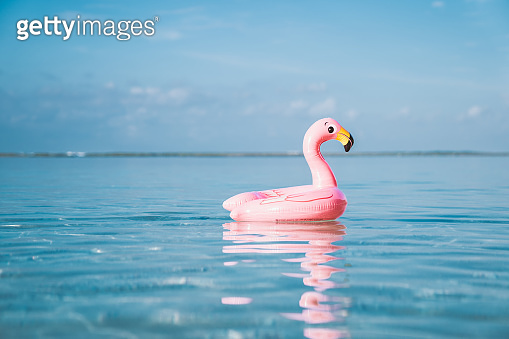 Inflatable pink flamingo floating at transparent turquoise sea. Blue sky with few clouds on the background.