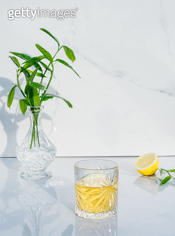 Crystal glass with yellow cocktail, vase with fresh greenery and half of lemon on marble background. Glass goblet with green tea, alcohol drink. Direct sunlight and shadows. Minimalism. Copy space.