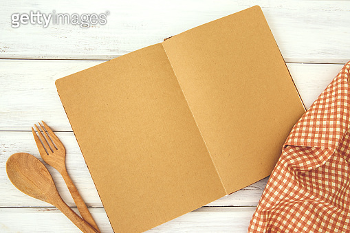 brown recipe cooking book on a white wooden bord