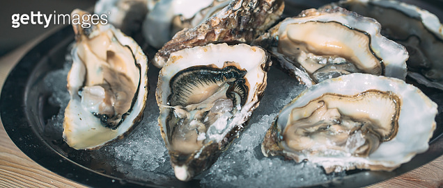 Oysters on a black plate on a wooden background.