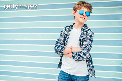 Fashion portrait of caucasian blonde hair 12 year old teenager boy dressed t-shirt and checkered shirt in blue sunglasses posing on turquoise blue background wall background. Teens fashion concept.
