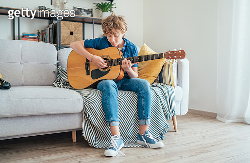 Preteen boy playing acoustic guitar dressed casual jeans, shirt and new sneakers sitting on the cozy sofa at home living room. Music education concept image.