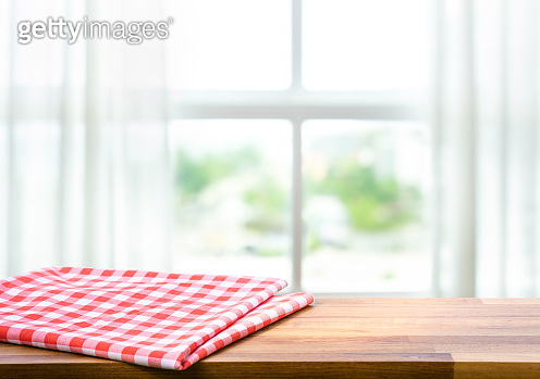 Red fabric,cloth on wood table top on blur window in morning background.For montage product display or design key visual