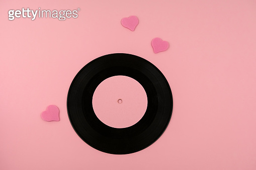 retro dusty vinyl disc with favorite songs and pink hearts