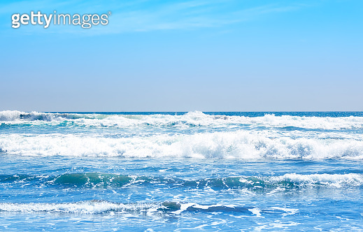 Blue ocean waves and yellow sand