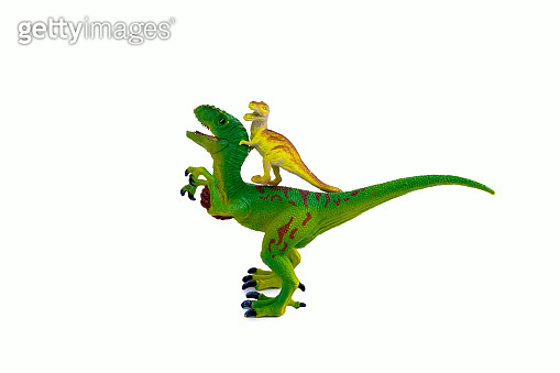 big green plastic toy dinosaur and small yellow dinosaur sitting on its back