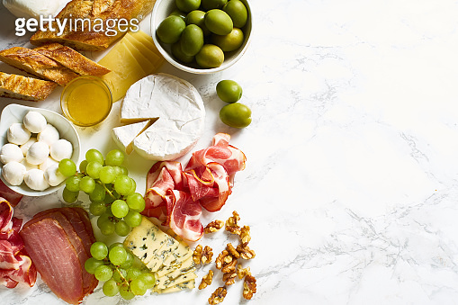 Cheese plate with brie, parmesan, cheddar and meat. Flatlay with variety of gourmet snacks, fruits and baguette on marble board. Copy space