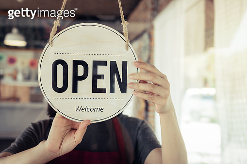 Reopen. barista or waitress woman turning open sign board on glass door in modern cafe coffee shop ready to service, cafe restaurant, retail store, small business owner, food and drink concept