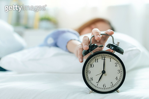 young asian woman sleeping on bed pressing snooze button on black vintage alarm clock at seven o'clock morning in bed room at home, lifestyle, good morning, healthy sleep and joyful weekend concept