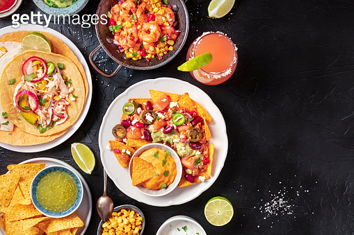 Mexican food, a flat lay on a dark background with copy space. Nachos, tortillas, Paloma cocktails, shot from above