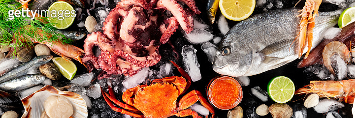 Seafood panorama, shot from above. Fish and octopus, scallop, crab, caviar. Gourmet products flat lay