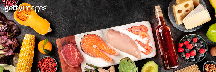 Food panorama on a black background with copy space. A flat lay of various products, shot from the top. Meat, fish, chicken and shrimps, vegetables and fruits, wine and cheese, with a place for text