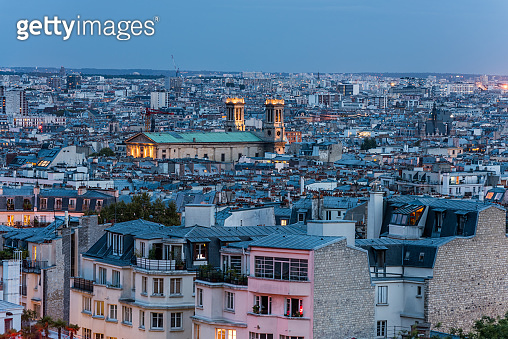 Aerial view of the old town of Paris at night, view from the The Basilica of the Sacred Heart of Paris, at the summit of the butte Montmartre, the highest point in Paris, France