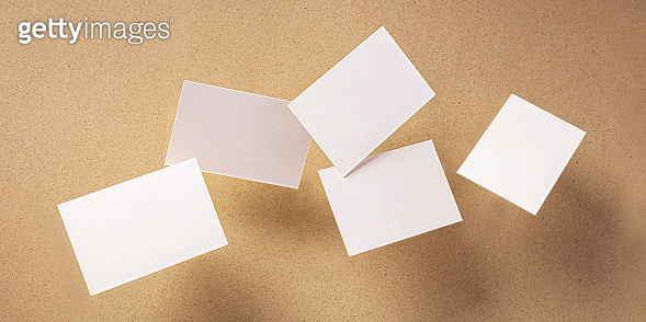 White thick business cards, flying on a brown paper background, a panoramic mock-up for design presentation