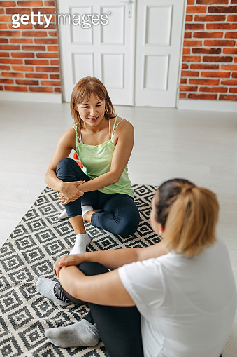 Two girlfriends exercising together at home