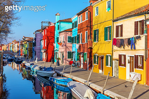 Street with colorful buildings in Burano island, Venice, Italy. Architecture and landmarks of Burano, Venice postcard. Scenic canal and colorful architecture in Burano island near Venice, Italy