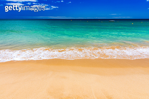 Soft wave of blue ocean on sandy tropical beach. Background of tropical paradise beach with golden sand, travel tourism panorama background concept. Sand and sea waves background.
