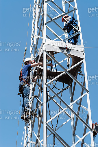 Construction work on the installation of a wind power plant. High-altitude installers perform installation work on the truss tower of the wind turbine