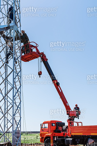 Installers carry out construction work on the installation of a wind turbine using an aerial platform