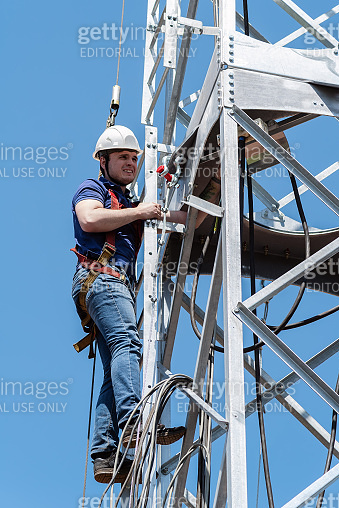 Construction work on the installation of a wind power plant. High-altitude installer performs installation work on the truss tower of the wind turbine