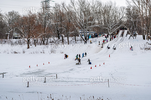 Winter bank of the Ural River with an ice slide for children to ride