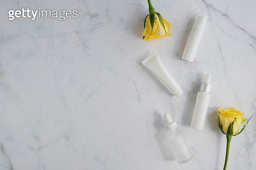 cosmetic skincare packaging . beauty product mock up on luxury white marble with yellow rose.