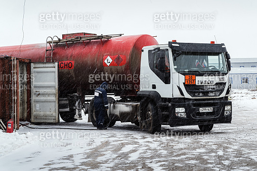 Oil tanker truck with a semitrailer tank is refueling. The picture was taken in Russia, in winter in snowfall