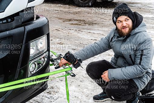 A videographer fixes a video camera on a bumper of a truck, winter
