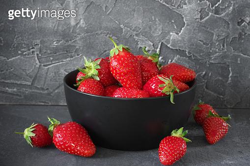 Fresh strawberries in black ceramic bowl on grey