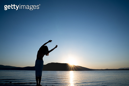 Silhouette of young Woman is stretching her body for morning sport or meditation against the beauty nature. Health and Tourism concept.