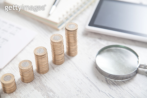 Stack of coins, magnifying glass, tablet, calculator.