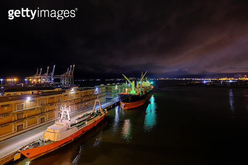 Big vessels at the port of Montevideo harbor with the beautiful nightsky of the cityscape skyline, Montevideo, Uruguay