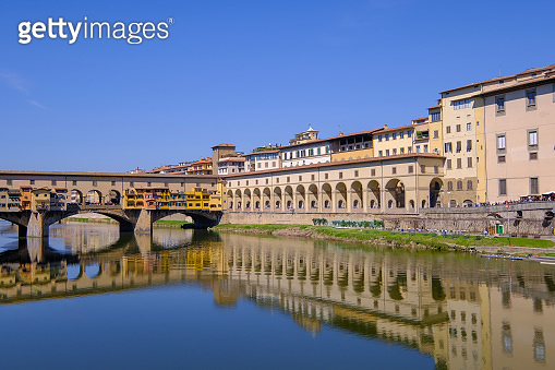 The famous Ponte Vecchio, the Old Bridge and city houses with reflections in the Arno River, Florence, Tuscany, Italy