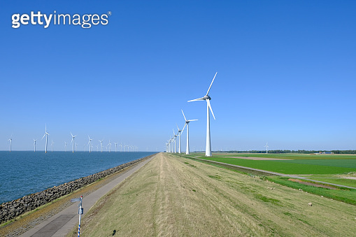 Wind turbines in a windpark on the shore of a lake in The Netherlands