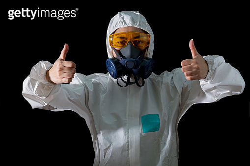 Woman thumb up sign in a chemical protective clothing and antigas mask with yellow glasses at the black background, Women scientist in safety suit, Safety virus infection concept