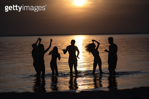 The people dancing at the evening beach party against the sunset