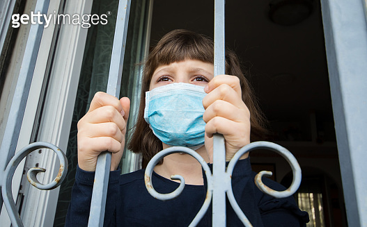 Coronavirus Young girl in  home isolation auto quarantine wearing face mask protective for spreading of disease virus looking out from the windows