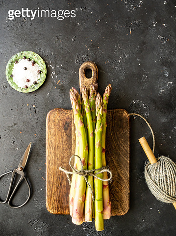 Fresh green asparagus on a cutting board, secateurs and yarn on a gray kitchen table