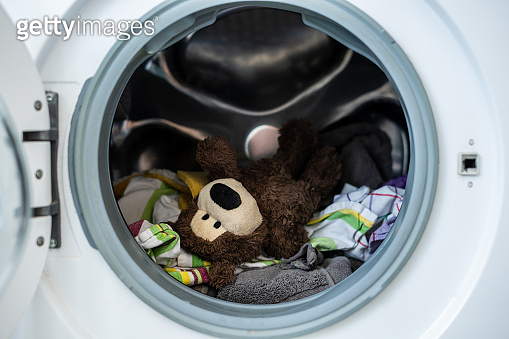 A brown teddy bear with dirty laundry in a washing machine