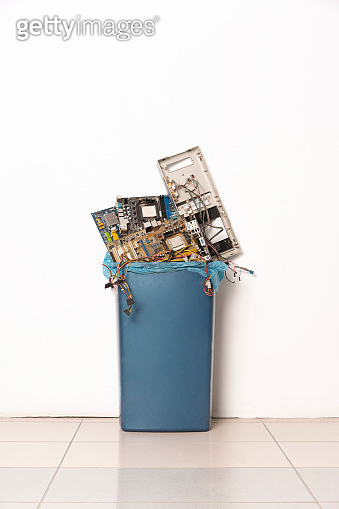 Plastic trash can full with pile of used, obsolete electronics