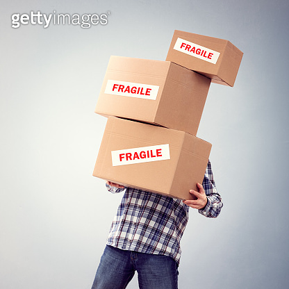 Man holding heavy fragile cardboard boxes relocation, moving house or courier delivery