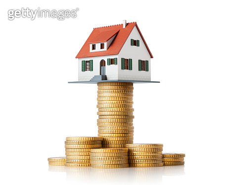 Miniature model house standing on a stack of coins