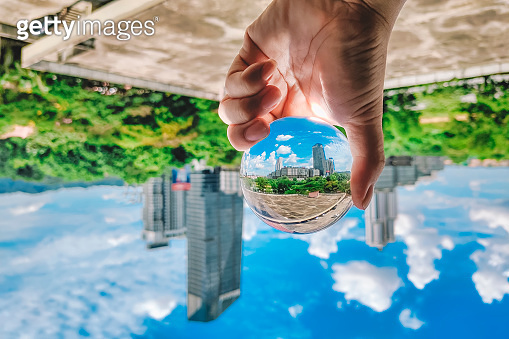 Scenery with blue sky cloud , building exterior and greed trees see through crystal ball