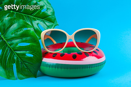 Inflatable watermelon on blue background with sunglasses and monstera leaves.