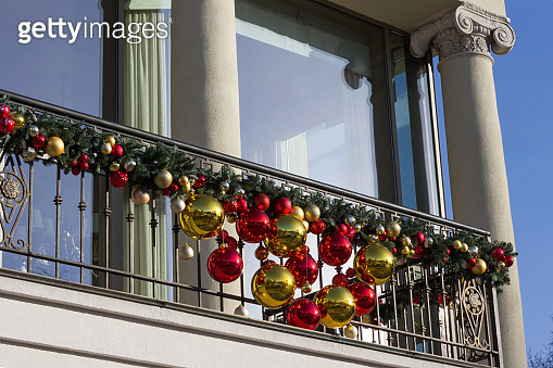Balcony railings are decorated with tree branches and toys