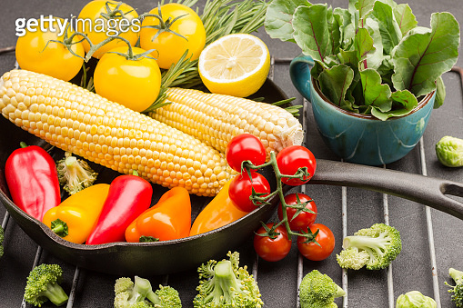 Multi-colored tomatoes,  sprig of rosemary, corn and peppers in pan.
